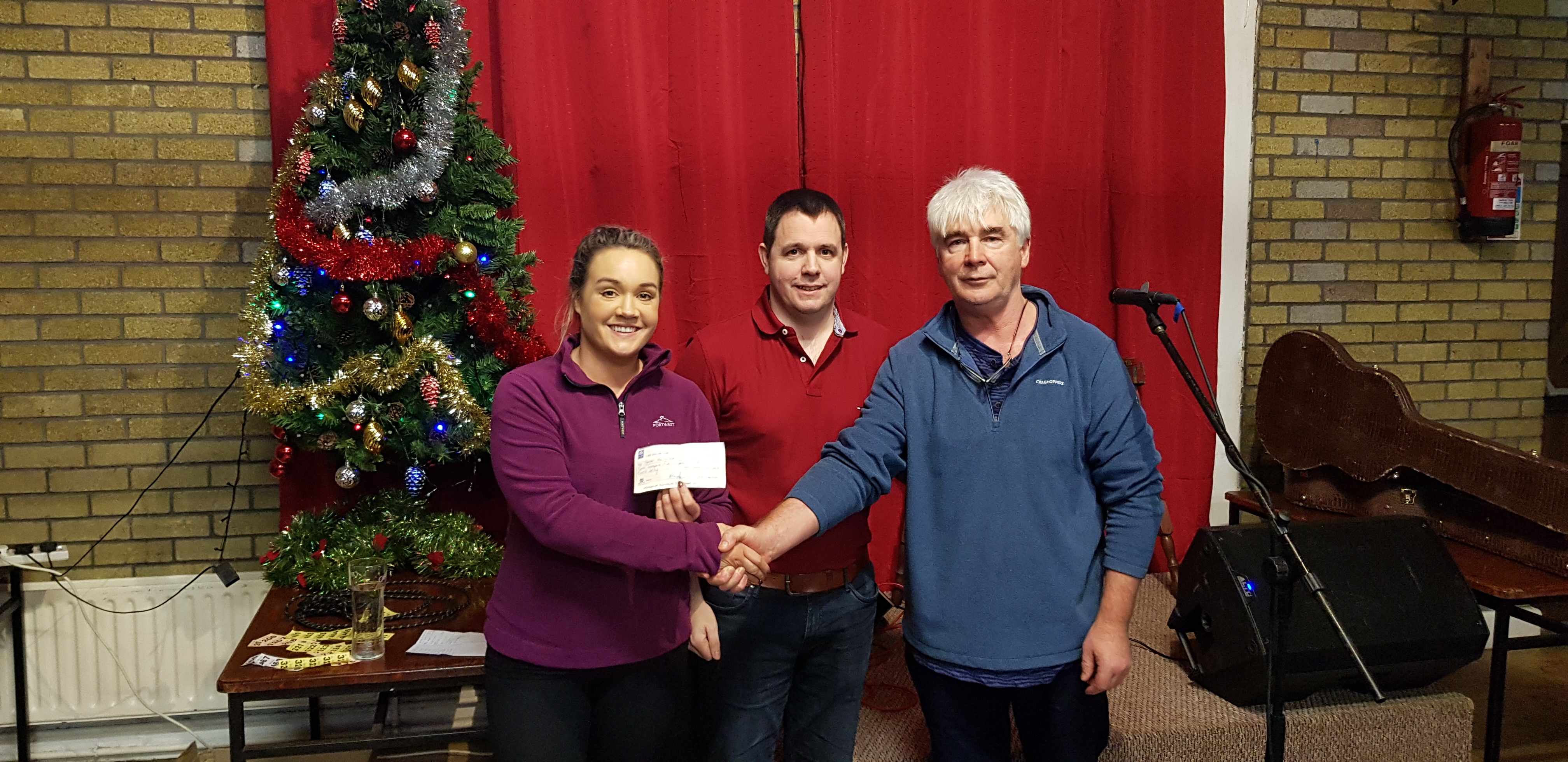 Ciara and Paul Kennedy accepting the cheque on behald of their brother John from Club Chairman John Spriggs