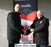 Leslie Doyle presents the O'Neills club of the week voucher to John Kennedy Passage