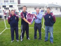Anthony Gill AGS presenting a set of jersies for the under 8s