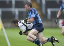Sean O'Shea, Arles Killeen is tackled by Ciaran Keegan, Ballyroan Abbey in the Laois Shopping Centre Senior Football Championshi