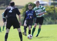 Mark Bogle passes the ball as PJ Mc Cenamin closes in during Castlefin Celtic's home match against Raphoe Town