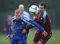 Milford United's Lee Burke and Donegal Town's Gary Harron in action
