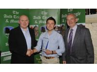 Amhlaoibh being presented with his tropy by Michael O'Riordan and Brendan Kenneally Awards Committee