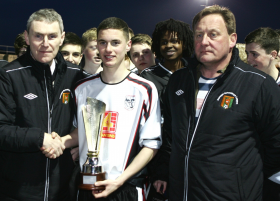 Ciarán Maloney picks up the Under-16 Champions League Trophy from Donegal Schoolboys League chairman Ian Curristan
