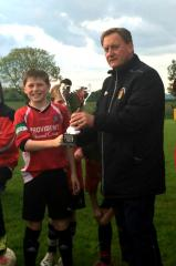 Keiran Tobin (Glencar U12s) receives the Letterkenny Premier Cup from Gerry Gallagher