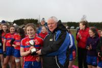 Cora Joy recives the Lidl Minster PPS Junior A Cup from Eamonn O Connor