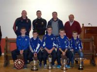 Hollymount/Carramore GAA Club players displaying some of the silverware