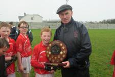 Brother James Dormer presents the County Shield to St Nessan's NS captain